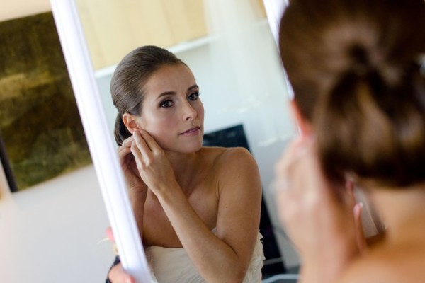 a bride checking out her makeup in a mirror