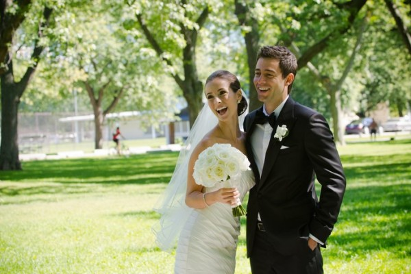 bride and groom laughing in a park