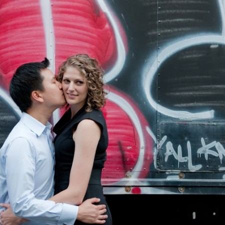 engaged couple in front of graffiti